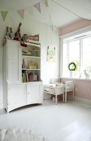 På övervåningen har trägolven målats vita. Theas mysiga rum går i rosa. I skåpet står mjuka djur och leksaker från Maileg.