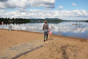 Miljöinspektör Anneli Johansson är på väg mot vattnet vid Norebadet, utrustad med vattenprovsflaska och protokoll.