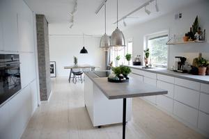 Köket har totalrenoverats och planlösningen blev en helt annan när väggen till det gamla finrummet togs ner. Ljusa väggar, vit köksinredning och bänkskivor i betong skapar en industriell och stilren känsla.