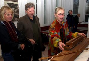 Boel Tengnér till höger visar Målar Olles psalmodikon för paret Ann-Catrine och Lars Klusell från Hälla Foto:Christer Klockarås