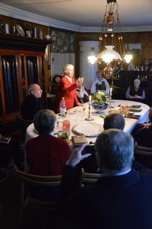 Flory Gren hälsar hembygdsföreningen Noraskog välkomna till Göthlinska gården där hon giudat i 50 år. Här berättar hon om lampan i matsalen med den lilla klockan som användes för att kalla på tjänstefolket.