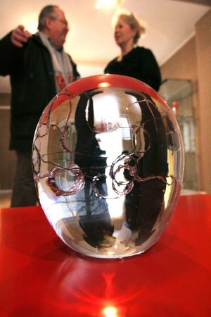 Den här glaskulan med koppartråd i har förmågan att vända upp och ned på världen. Samlaren och glaskännaren Tord Turesson är en av besökarna, som gärna diskuterar glas med Monica Domert.
