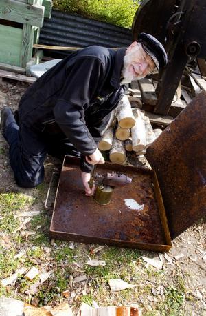 Anders Berggren värmer först den stora blåslampan som i sin tur används för att värma tändkulan på motorn.