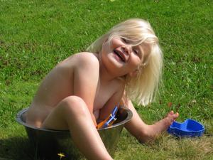 Tycker denna bild är helt underbar på vårt barnbarn Vera som är 3 år. Hon var med famor och farfar i sommarstugan sista helgen i juli. Det blev en väldigt solig stund och ingen pool fanns så farmor letade fram en gammal tvättbalja i rostfritt, hällde i ljummet vatten i den och Vera blev glad.