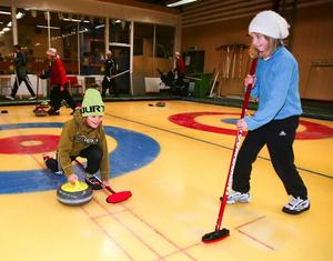 På onsdagskvällarna mellan 18 och 19 är Curlinghallen i Östersund fylld av unga och barn från 9 år och uppåt.Linnea Krusenberg har på kort tid blivit en fena på att glida iväg med curlingstenen. Och Linnéa Svedberg är redan duktig på att sopa så att stenen glider längre. Båda bor i Valla på Frösön.