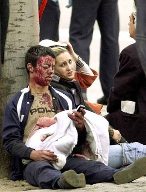 Two people injured by an explosion in a train wait for aid outside the train station of Atocha in Madrid, Spain, Thursday, March 11, 2004. At least 30 people were killed in just one of three Madrid train station blasts, a Spanish news agency reports. (AP Photo/Jose Huesca/EFE) ** SPAIN OUT **