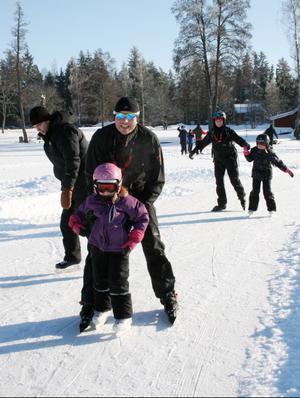 Fyraåriga Kajsa Fange får hjälp av pappa Peter på sina allra första skridskodag. Bakom dem på Långforsens is kommer Andreas Jans samt Ulrika pch Klara Fange.Foto: Ingalill Forss Norberg