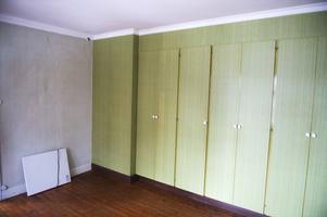 Bakom garderoberna döljer sig en kakelugn.