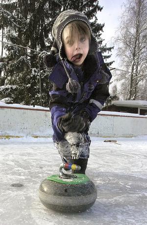 Liten kille med stor sten. Adrian Hansson Bånga heter han som tar i för kung och fosterland vid curlingen.