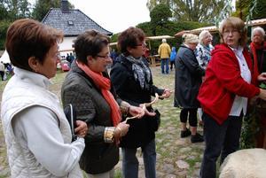 Lena Nilsson i röd jacka förklarar för Gun Stoltz i mitten om hur skatskrämma fungerar. Gun Stoltz slog till och fick med sig en hem.