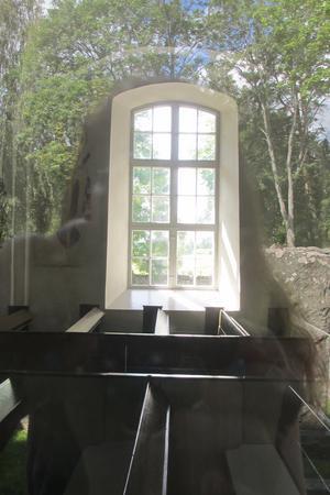Både interiör och exteriör från Kärrbo kyrka. Jag tog en bild utifrån,in genom fönstret - och fick då både med kyrkans innandöme och naturensom speglade sig i fönsterglaset utifrån.