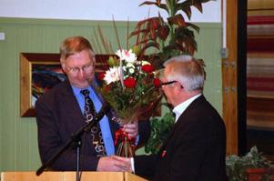 Lennart Olsson avtackades med blommor under sitt sista fullmäktigesammanträde i rollen som kommunstyrelsens ordförande. Blommorna överräcktes av fullmäktiges ordförande Billy Andersson. Foto: Carin Selldén