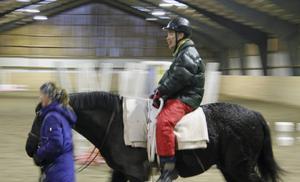 Jocke Wallin spricker upp in ett stort leende när Karin Alsiö springer så handikapphästen Dilton travar.