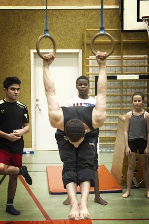 Parkourläraren Ibrahim Tunc visar hur man kan hänga i ett par romerska ringar.