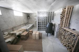 Där nere finns en rymlig spaavdelning med bastu, dusch, bad och öppen braskamin.