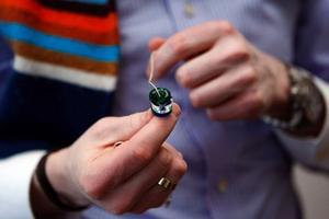 """Det här smycket säljs till Designtorget i Stockholm. De tre små ringarna som sätts på halskedjan kan köpas i de färger kunden så behagar. Längst ut på ena ringen står ett litet budskap, till exempel """"Save the children"""". En del av intäkterna går till välgörande ändamål. Magnus Norberg har designat smycket."""