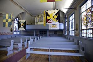 Kyrkan är rikt utsmyckad med fanor i salen.