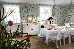 """""""Jag har alltid gillat den vita, lantliga stilen"""", säger Helena Tjernström.                  Tapeten i matrummet heter Sweet Bay och är från Sanderson, kopparlamporna är från Strömshaga. Matgruppen köptes på Mio för några år sedan, medan övriga stolar är olika loppisfynd. Så också skänken som Helena målat vit."""