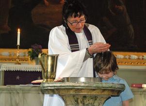 Komminister Birgitta Lagerqvist döper Maximilian Nylin som var nummer två i raden av barn som i lördags döptes på löpande band i Gustafs kyrka.