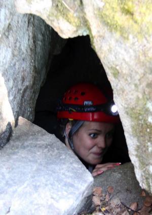 Linnea Ögren letar sig ut ur en grottgång.