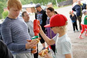 Efter rallyt var det varmkorvservering. Sam Bäck häller ketchup på Noah Jönssons varmkorv.