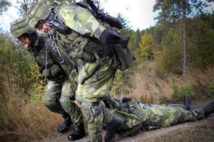 De skadade soldaterna i det första fordonet släpas bakåt, för att sedan kunna transporteras vidare till läkare.