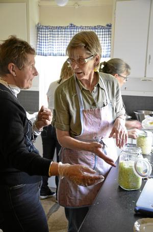 Höststök. Ulla Bergkvist får hjälp av Berit Karlsson att göra i ordning sin burk med vitkål som ska mjölksyras.