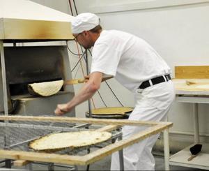 Gräddningen sker i en så kallad Hammerdalsugn, där Joakim här tar ut en färdig brödkaka.