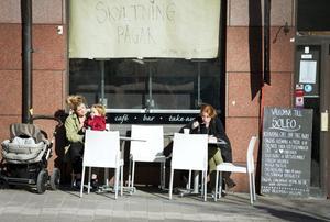Första uteserveringen. Malin Liljeroth och sonen Frans tar en fika på Våghustorgets första uteservering. Johanna Bengtsson sitter också där och äter lunch och läser en bok.