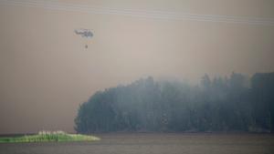 En helikopter vattenbombar eldfronten som nått till sjön Snyten.