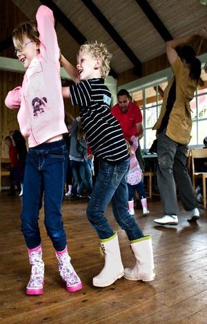 Astrid Gunnarsson och Viggo Vedin dansar ringdans så att det står härliga till. Många förtjusta skratt blir det under