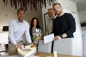 Martin Hagman och Dan Löfgren, mitten, överlämnar tårta, blommor och present till Norrtälje kommuns invånare nummer 57 000 till Frida Ahlström och Nicklas Hellborg.