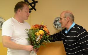Märkbart rörd och berörd var Anders Runnkvist när människor från uppväxtbyn Högfors visade uppskattning. Här lämnar Stig Fjälling över blommor och gratulationer.