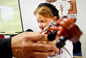 Fanny Berggren, åtta år gammal får prova på violin. Men hon tyckte ännu mer om att spela cello. Här ger läraren Johan Sirén henne en hjälpande hand.