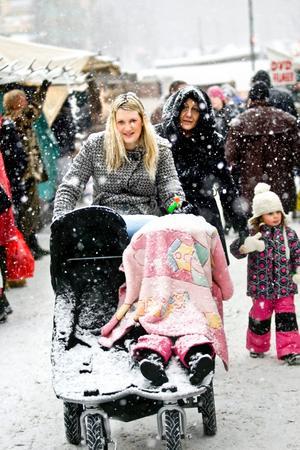 Snön föll tung över marknadsbesökarna på onsdagen. Här kämpar sig Anna Wallin fram med vagnen. I bakgrunden syns Vartina Singh.