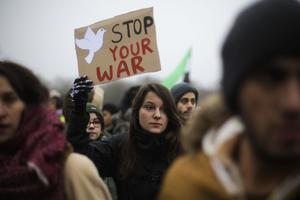 En kvinna protesterar mot kriget i Syrien, i Tyskland. Flera av vårens böcker skildrar krig, flyktingar och den dystra samtiden. Arkivbild.