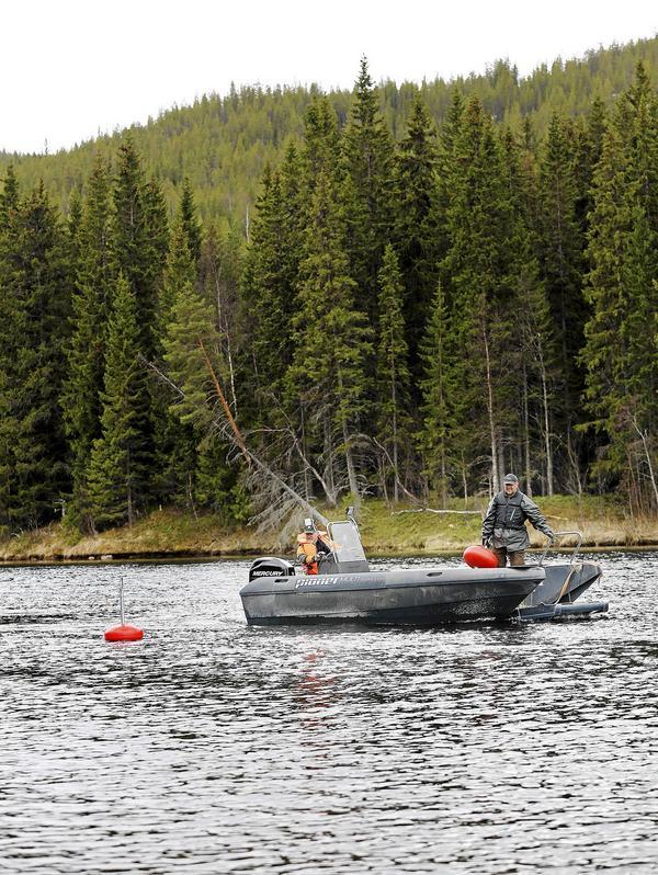 Allan Blomkvist och Per-Ola Persson använder Långåfiskets stora arbetsbåt för att lägga ut bojar där fiskare kan förtöja och fiska av området.