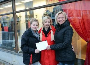 Fr v vinnaren Camilla Klingstam, affärsinnehavaren Lissdaniels Anna Roberts och centrumledaren Annika Nouvel med det vinnande skyltfönstret i bakgrunden.