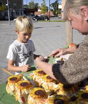 Brer på. Benjamin Lagerlöf får hjälp att breda på lite getost på en hård brödbit. Carla Booÿ har tillverkat osten.