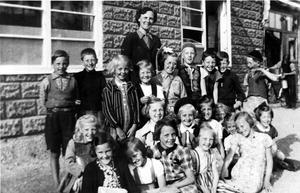 Småskolan på Skiljebo. Där Nurmis bilverkstad nu ligger var det skola och livsmedelsaffär. Fröken hette Eivor Donner och kortet togs 1941 eller 1942. Flickan med vitt hårband, framför lärarinnan, heter Gun Persson och andra pojken från vänster är Arne Lindgren.