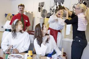 """""""Håll i håret. Ett, två, tre!"""" säger Anna Sörensson som bryskt rycker av luciakronan som fastnat i håret på Linnéa Edvinsson på grund av all stearin som har runnit."""
