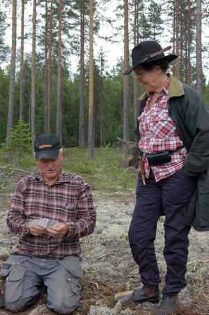 Tore Berglund från Föne fornminnesförening visar utgrävningsfynd för en besökare som kom för att titta på utgrävningarna.