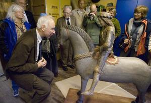 Den medeltida skulpturen av S:t Göran i Hälsingtuna kyrka har konserverats och konstprofessor Jan Svanberg beundrar detaljarbetet på nära håll.