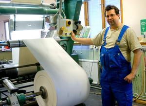 Tapetrulle. En gigantisk tapetrulle ska skäras upp i ark till tapetböckerna, en process Jan Olofsson sköter om.