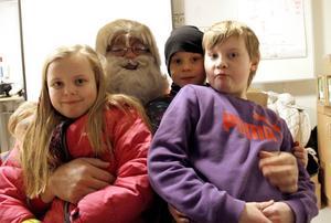 Line Elofsson, 9 år, Oliver Skoglund Björkholts, 9 år, och hans bror Pontus, 11 år, fick sitta i Gästriketomtens knä.