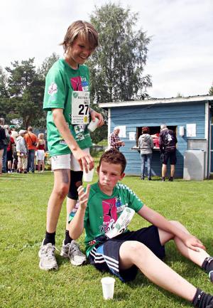 Elias Westin, Ås, ger Rasmus Näslund, Kramfors, vatten efter målgången i Bäverloppet.