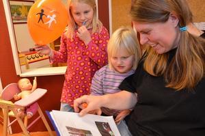 Pärmtitt. På förskolan med de allra yngsta är det konstutställning, vernissage, uppträdande. Här är det Ingrid Daugaard, storasystern Hilda och deras mamma Evelina som kollar in förskolans pärm.