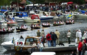 Fullt efter strandkanterna. Många båtar hade lagt an efter strandkanten i Lillälven. Efter kyrkbåten kom sex mindre roddbåtar med saker till midsommastången.