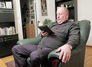 Larz Gustafsson läser hellre böcker än firar jul. Här läser han i bibeln.
