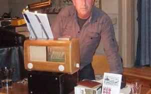 Jan-Olov Nilsson med tidstypisk radio och boken Red Dog som han skrivit och som handlar om bland annat Rättvik.